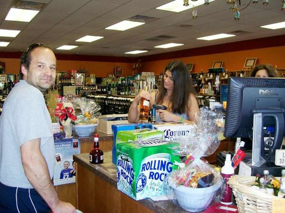 Photo by Lynn Fredricksen Vines Distinctive Wine & Liquor owner Daniela Tristine rings up customer Dusan Velickovic at her store at 323 Washington Avenue.