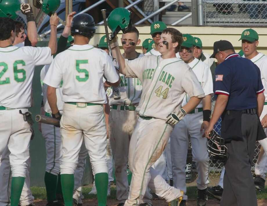 Notre Dame's Dave Beisler is greeted by teammates after hitting a home run against North Haven. While the Green Knights lost that game, 5-4, Beisler earned the win on the mound the previous day in Notre Dame's thrilling 6-5 comeback victory over Shelton. (Photo by Russ McCreven)