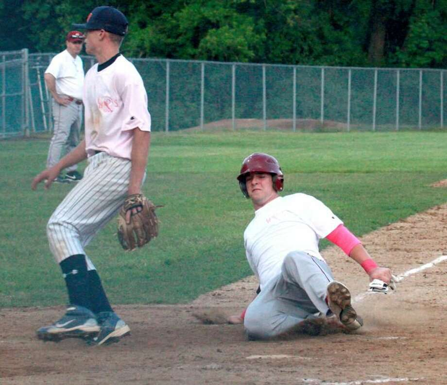 Sheehan's T.K. Kiernan slides home safely for a run in the Titans' 9-0 victory over cross-town rival Lyman Hall last Friday night at Pat Wall Field. Both teams wore pink to promote Breast Cancer Awareness. (Photo by Russ McCreven)