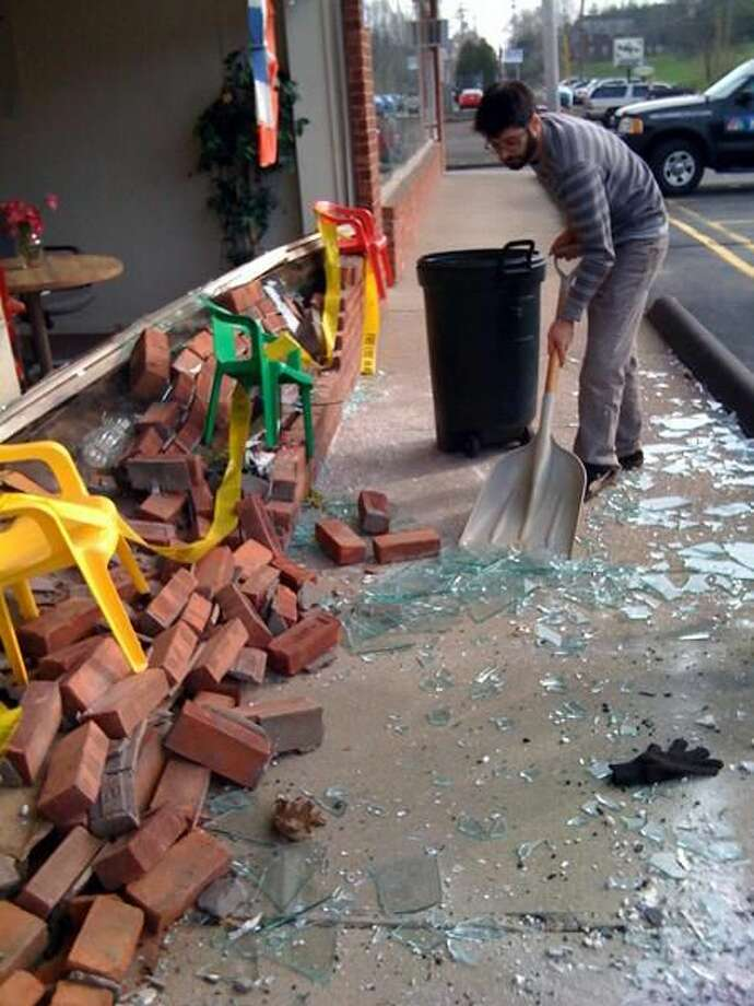 Photo by Ann DeMatteo/Register John Brandon Benevento, owner of King Acres Plaza, cleans up after a vehicle slammed into the wall of CT Presort on Wednesday. This was the second time in less than a week that a vehicle hit a business in North Haven.