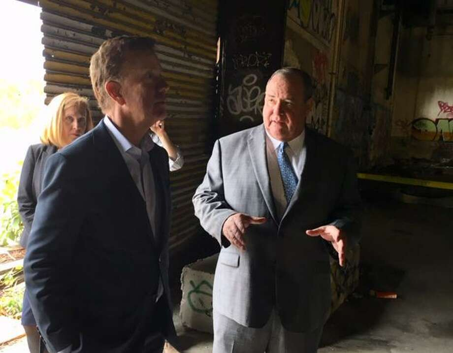 Gov. Ned Lamont listens to a pitch by Mayor Neil O'Leary in the abandoned Anamet factory. Photo: Mark Pazniokas / CTMirror.org