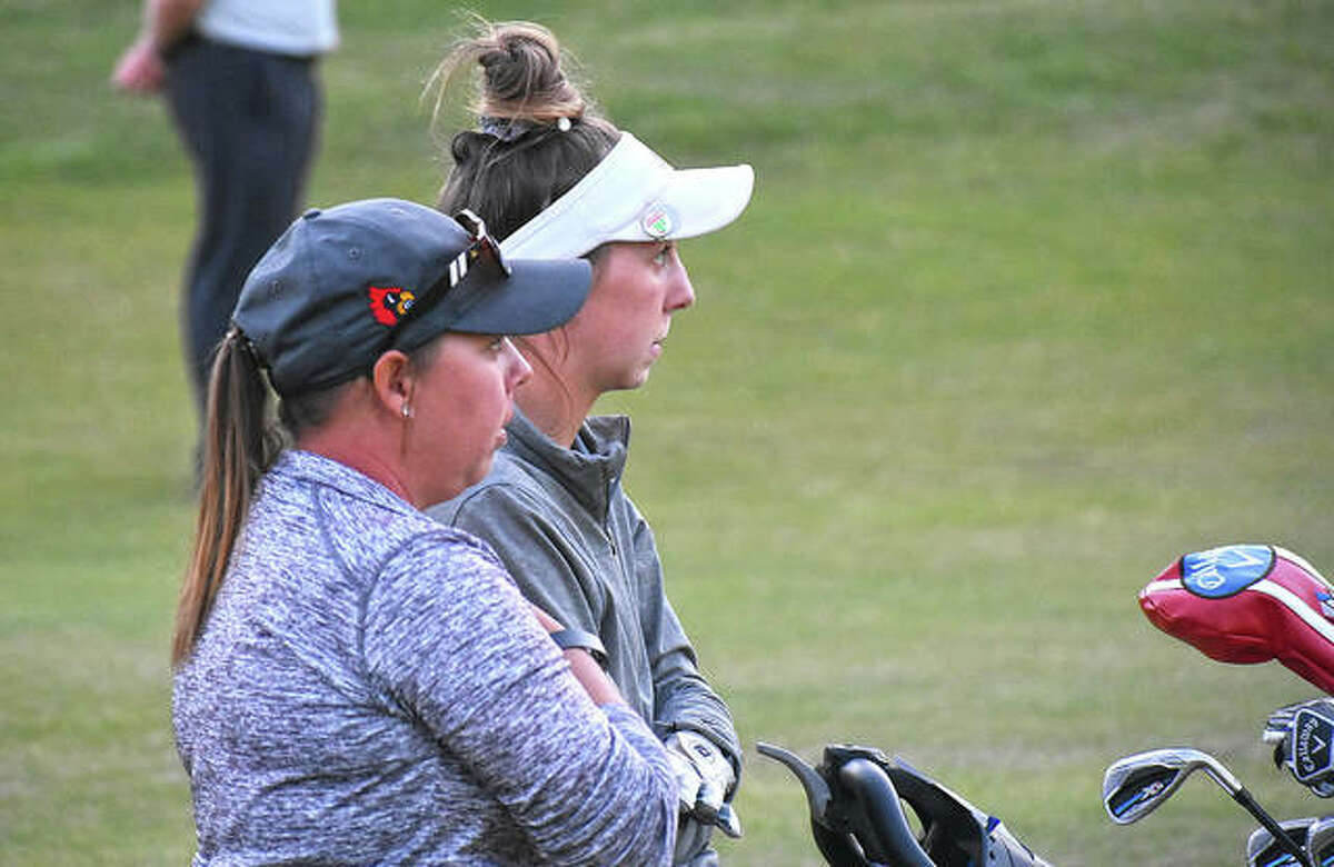 Alton's Natalie Messinger (right) and Redbirds coach Carey Cappel discuss Messinger's next shot Monday at the Class 2A sectional at Far Oaks in Caseyville.
