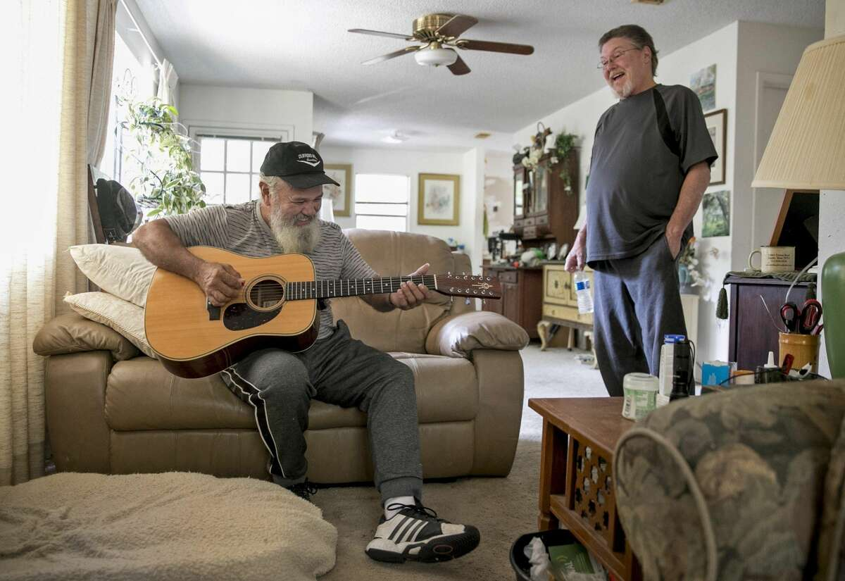 Coy Featherston plays guitar in the home of his longtime friend Don Vanderburg in Lago Vista on Wednesday.