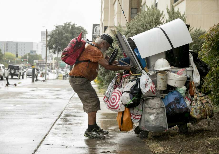 Coy Featherston, 68, who has been homeless since 1995, quickly moves his belongings out of the rain from his camping spot on Guadalupe Street and West 21st Street in the west campus neighborhood on Tuesday September 10, 2019. Photo: JAY JANNER/AMERICAN-STATESMAN/TNS
