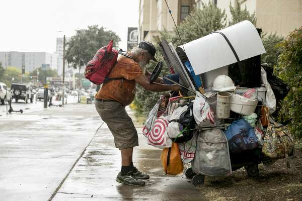 Coy Featherston, 68, who has been homeless since 1995, quickly moves his belongings out of the rain from his camping spot on Guadalupe Street and West 21st Street in the west campus neighborhood on Tuesday September 10, 2019.
