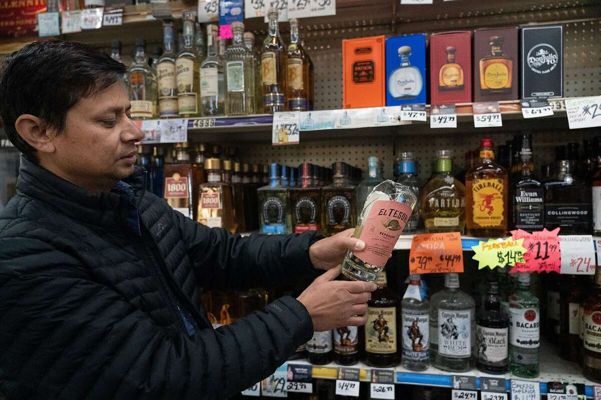 Rajib Karki looks at a $50 bottle of Tequila cleaned up from the earthquake damage at One Stop Liquor and Food on Tuesday, Oct. 15, 2019, in Pleasant Hill, Calif.
