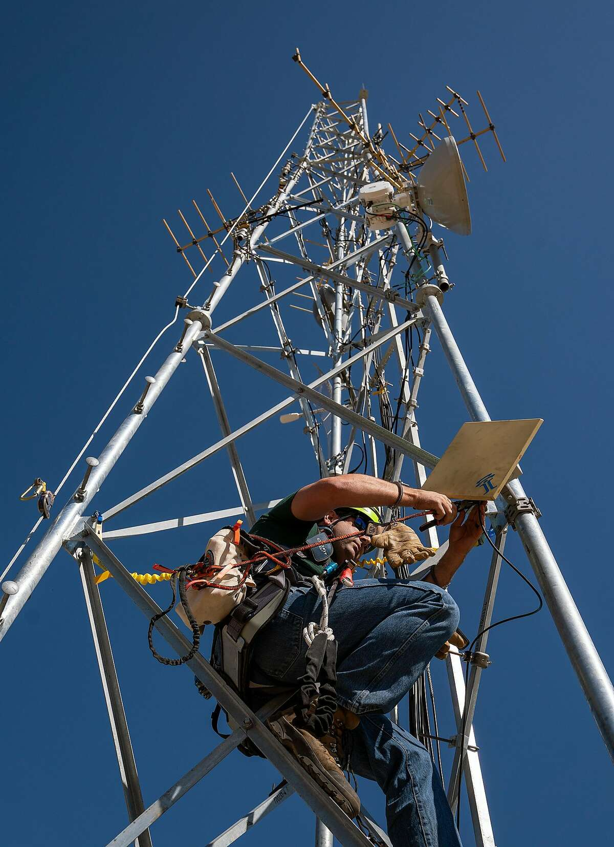 USGS RF Electronics Technician Darren Gray adds a cable support to a microwave radio mounted on a radio communication tower at the USGS earthquake monitoring site on Carr Hill on Wednesday, October 9, 2019 in Parkfield, Calif.