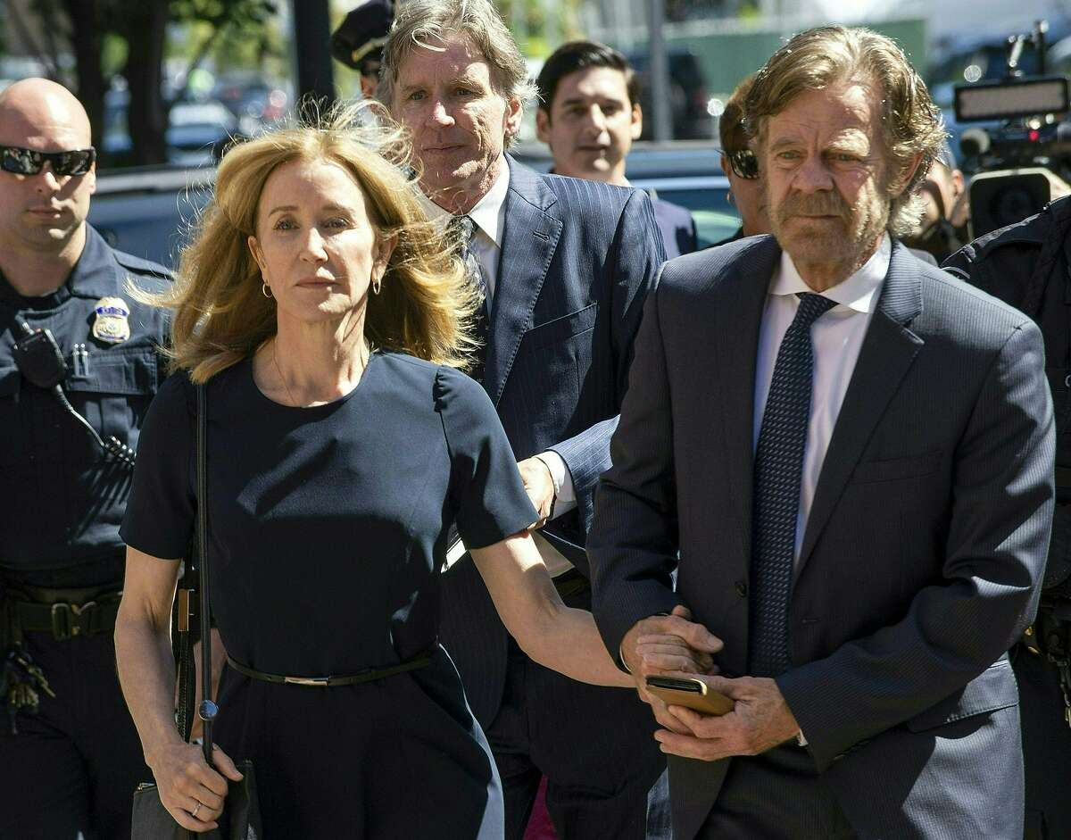 TOPSHOT - Actress Felicity Huffman, escorted by her husband William H. Macy, makes her way to the entrance of the John Joseph Moakley United States Courthouse September 13, 2019 in Boston, where she will be sentenced for her role in the College Admissions scandal. - Huffman, one of the defendants charged in the college admissions cheating scandal, is scheduled to be sentenced for paying $15,000 to inflate her daughters SAT scores, a crime she said she committed trying to be a good parent. (Photo by Joseph Prezioso / AFP)JOSEPH PREZIOSO/AFP/Getty Images