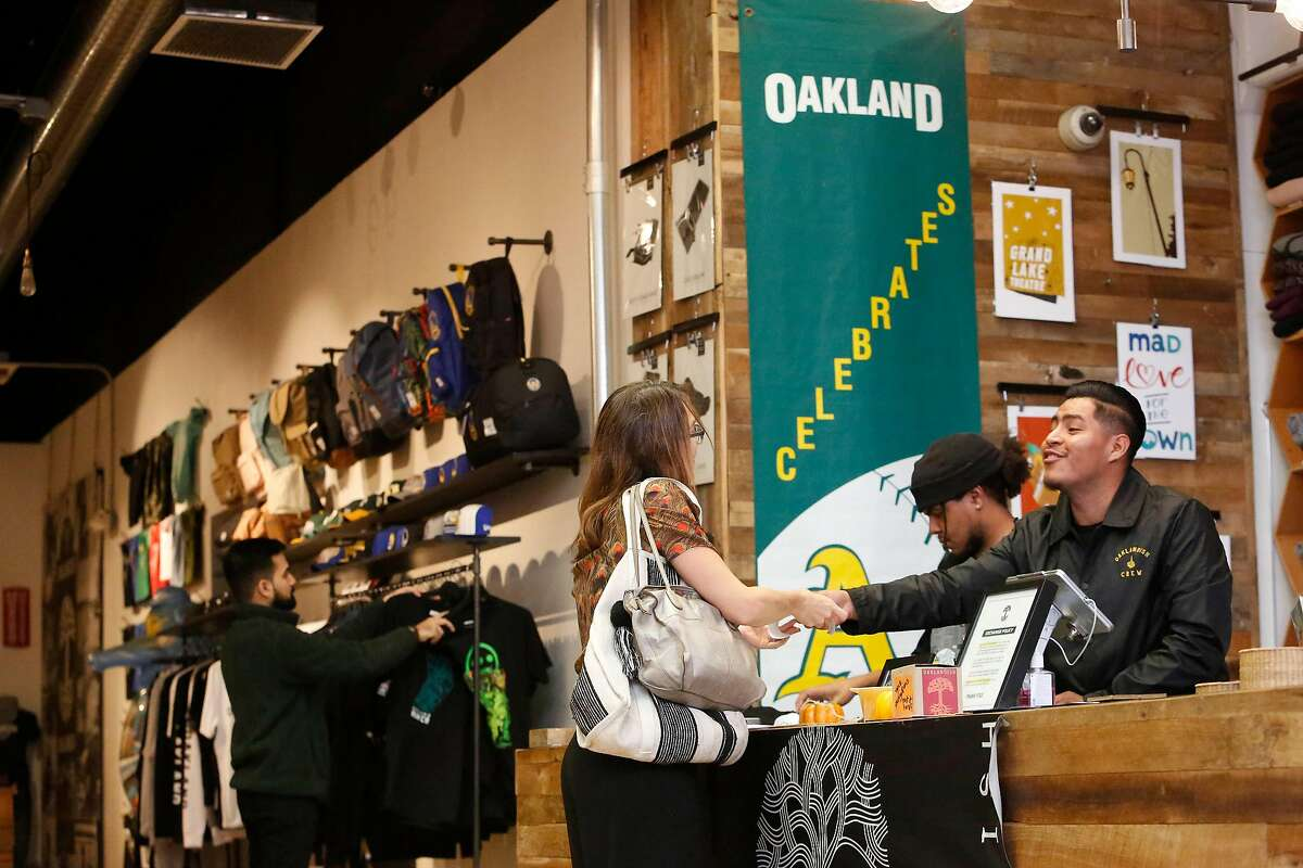 Richard Lorenzo (right), Oaklandish key holder, assists Chris Reed (right), of Oakland at the Oaklandish store on Broadway on Monday, October 14, 2019 in Oakland, Calif.