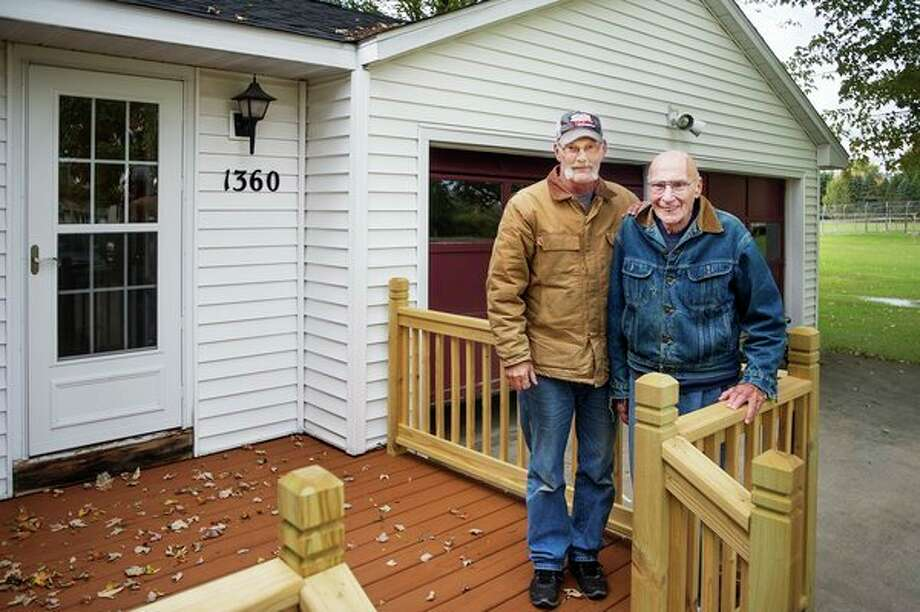 George Hartnagle, 85, right, and Mark Kloha, left, pose for a portrait Monday on the front deck at Hartnagle's home, which has a brand new railing thanks to help from Kloha. (Katy Kildee/kkildee@mdn.net)