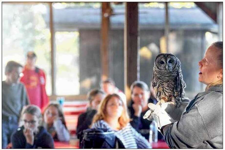 Kelly Vandersand, fundraising coordinator for TreeHouse Wildlife Center, speaks to the Neighborhood Guys and Gals 4-H Club in Winchester on Monday while Chili the barred owl patiently sits on her hand. The center will host OwlFest on Oct. 19-20.