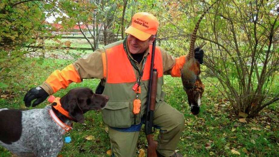 In this file photo from a past year, outdoors writer/editor Bill Parker and his dog, Brady, enjoy hunting wild rooster pheasants in the Thumb on the October 20 opener. (Tom Lounsbury/Hearst Michigan)