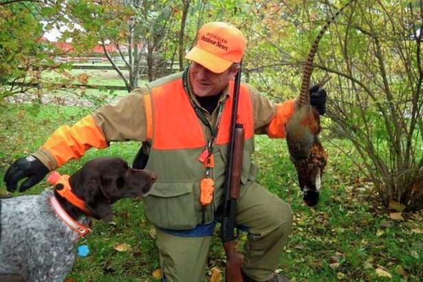 In this file photo from a past year,outdoors writer/editor Bill Parker and his dog, Brady, enjoy hunting wildrooster pheasants in the Thumb on the October 20 opener. (Tom Lounsbury/Hearst Michigan)