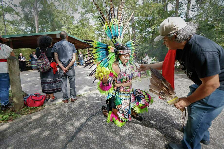 Maribel Garcia receives a smudging — a ceremony in which herbs are burned — from Eddie Garcia during Indigenous Peoples' Day on Monday at Jesse H. Jones Park and Nature Center near Humble. Photo: Steve Gonzales, Houston Chronicle / Staff Photographer / © 2019 Houston Chronicle