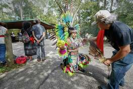 Maribel Garcia receives a smudging - a ceremony in which herbs are burned - from Eddie Garcia during Indigenous Peoples' Day on Monday at Jesse H. Jones Park and Nature Center near Humble.
