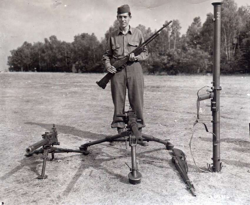 Technical Sgt. Francis S. Currey, Company K, 120th Infantry Regiment, 30th Infantry Division, poses July 26, 1945 with the weapons he used while halting a German attack on his company December 21, 1944 during the Battle of the Bulge. He received the Medal of Honor at Camp Oklahoma City redeployment center near Reims France.