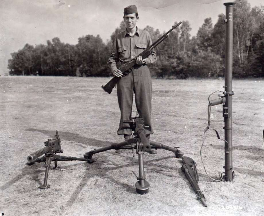Technical Sgt. Francis S. Currey, Company K, 120th Infantry Regiment, 30th Infantry Division, poses July 26, 1945 with the weapons he used while halting a German attack on his company December 21, 1944 during the Battle of the Bulge. He received the Medal of Honor at Camp Oklahoma City redeployment center near Reims France. Photo: National Archives Photo