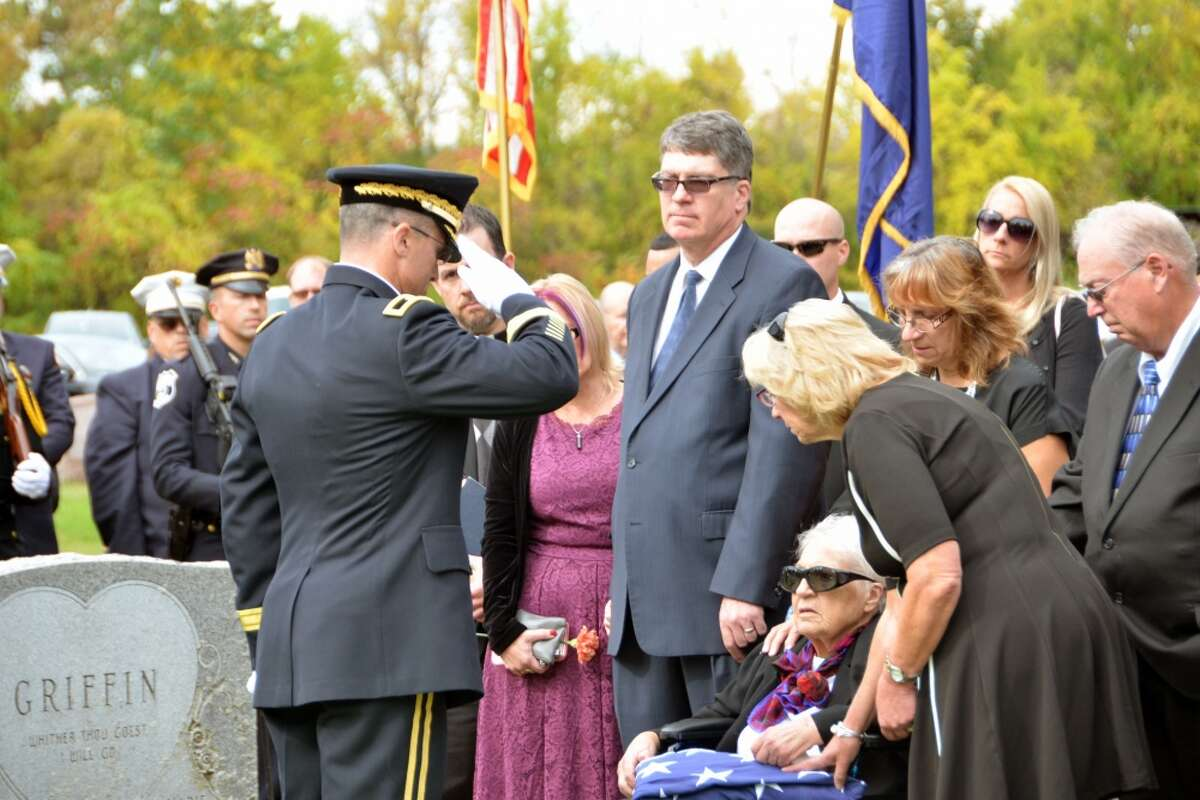 Army Brig. Gen. Brett Funck, Deputy Commanding General of the 10th Mountain Division, presents the colors from the casket of Army Medal of Honor recipient Tech. Sgt. Francis S. Currey to Currey's widow Wilma at the Mt. Pleasant Cemetery in South Bethlehem, N.Y., October 12, 2019. Currey, 94, from Selkirk, N.Y., died October 8. He received the Medal of Honor for valor displayed as an infantryman during the Battle of the Bulge in World War II. Members of the New York Military Forces Honor Guard provided military honors for the funeral service. (U.S. National Guard photo by Col. Richard Goldenberg.)