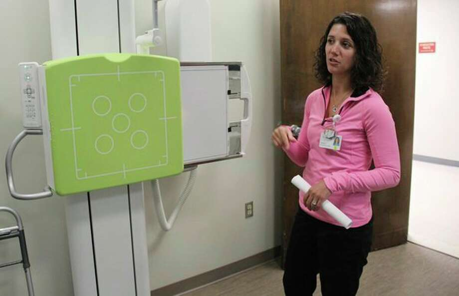 Kayla Harwood explains how McLaren Hospital's new X-ray machine works. The X-ray imaging room is one of many recent additions to the hospital. (Robert Creenan/Huron Daily Tribune)