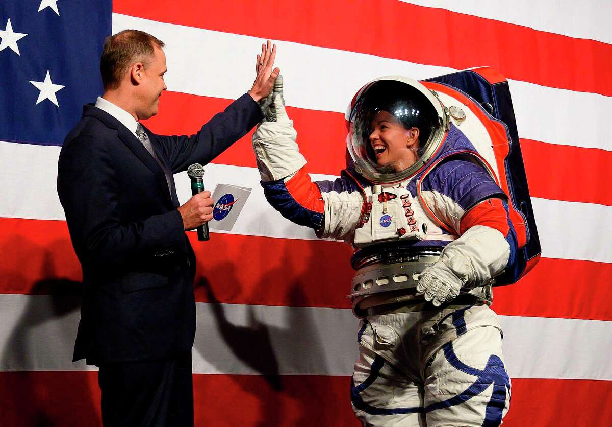 NASA administrator Jim Bridenstine (L) welcomes Advance space suit engineer, Kristine Davis (R), to the stage during a press conference displaying the next generation of space suits as parts of the Artemis program in Washington, DC on October 15, 2019. (Photo by Andrew CABALLERO-REYNOLDS / AFP)