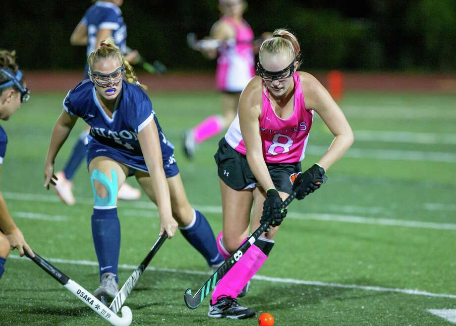 Bailey Harriott (8) keeps the ball away from a Wilton player during a recent field hockey game. Photo: Gretchen McMahon / For Hearst Connecticut Media