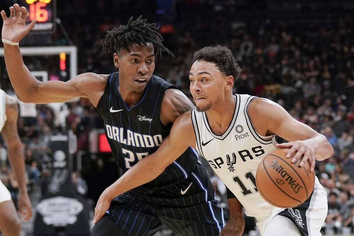 San Antonio Spurs' Bryn Forbes (11) drives against Orlando Magic's Wes Iwundu during the second half of an NBA preseason basketball game, Saturday, Oct. 5, 2019, in San Antonio. (AP Photo/Darren Abate)