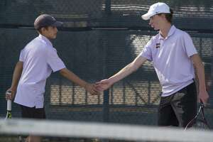 Tyler Stewart and doubles partner Connor Carriger take a moment between sets 10/15/19 as MHS takes on El Paso Americas in the 6A bi-district playoff at Midland High tennis courts. Tim Fischer/Reporter-Telegram