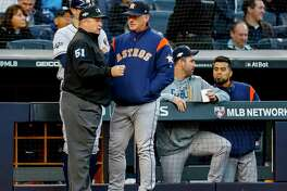 Houston Astros manager AJ Hinch (14) talks with umpire Marvin Hudson (51) after home-plate umpire Jeff Nelson had to leave the game after being hit in the mask by a foul tip during the fourth inning of Game 3 of the American League Championship Series at Yankee Stadium in New York on Tuesday, Oct. 15, 2019.
