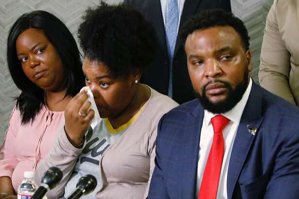 Amber Carr, center, wipes a tear as her sister, Ashley Carr, left, and attorney Lee Merritt, right, listen to Amber and Ashley's brother Adarius Carr talk about their sister Atatiana Jefferson during a news conference, Monday, Oct. 14, 2019, in downtown Dallas. Jefferson was shot and killed by a white police officer in her Fort Worth home as she played video games with her 8-year-old nephew. (Irwin Thompson/The Dallas Morning News via AP)