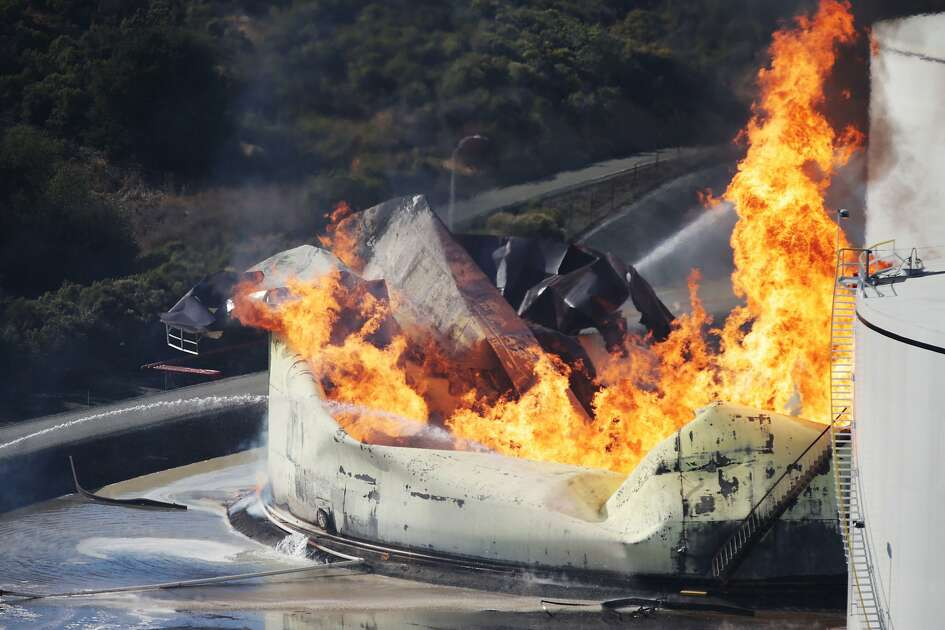 A tank burns as fire breaks out at a refinery in Crockett, Calif., on Tuesday, Oct. 15, 2019. A fire burning at an oil storage facility in the San Francisco Bay Area prompted a hazardous materials emergency that led authorities to order the residents of two communities to shelter in place and stay inside with all windows and doors closed. Contra Costa Fire Department spokesman Steve Hill said that an hour into battling the blaze, firefighters seemed to be making progress and were continuing to keep adjacent tanks cooled with water. (Anda Chu/San Jose Mercury News via AP)