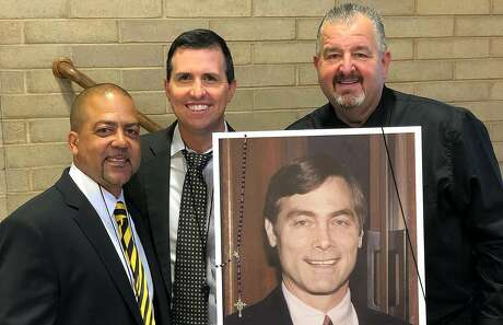 L-R Lou Richie, Tony Freccerro and Mike Banister, all former players and assistants of Bishop O' Dowd basketball coach Mike Phelps stand with a photo of Mike Phelps at a memorial in Oakland, Calif. on Monday, October 14, 2019.