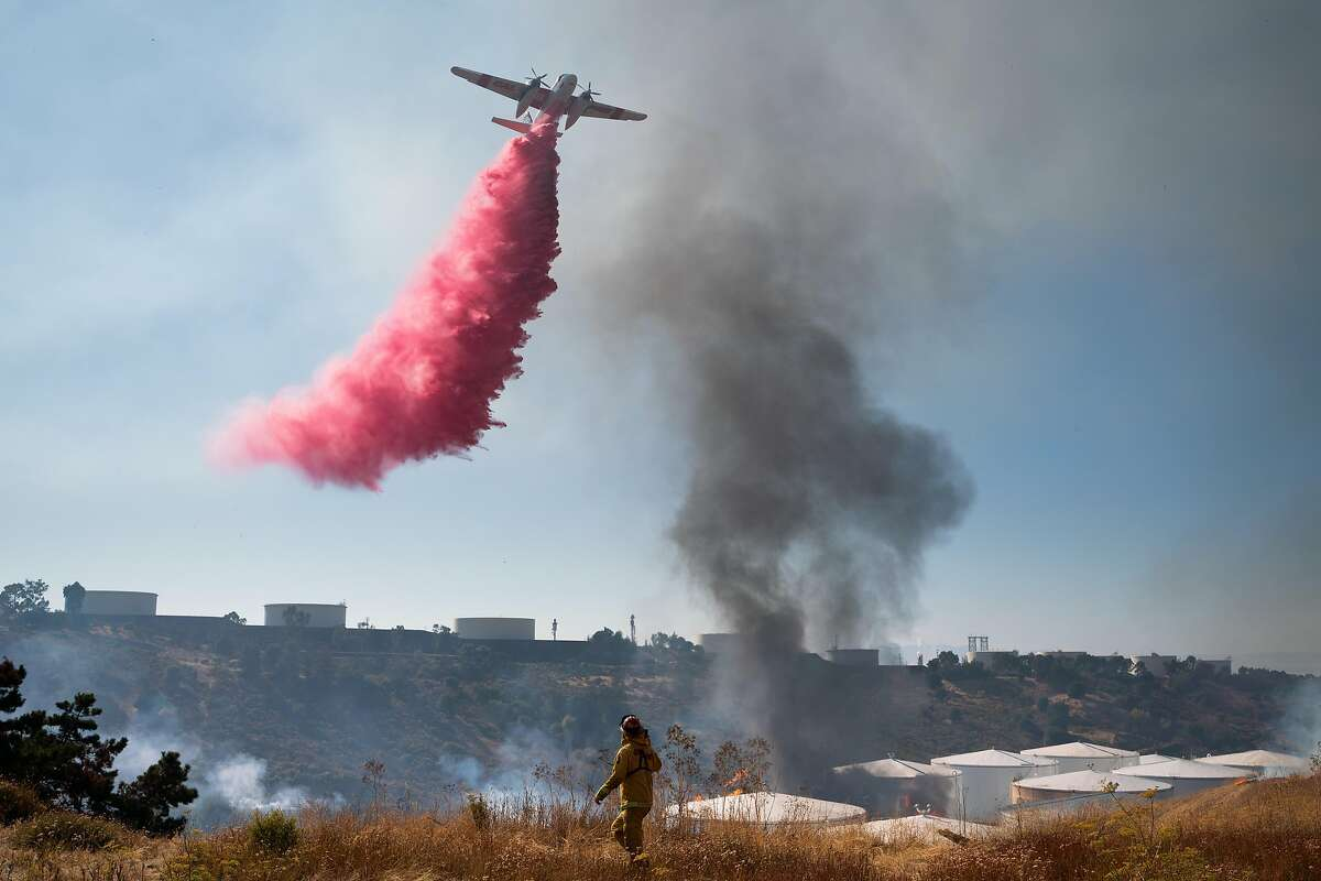 A Cal Fire airplane drops retardant onto flames at NuStar energy facility in Crockett, Calif. on Tuesday, Oct. 15, 2019.