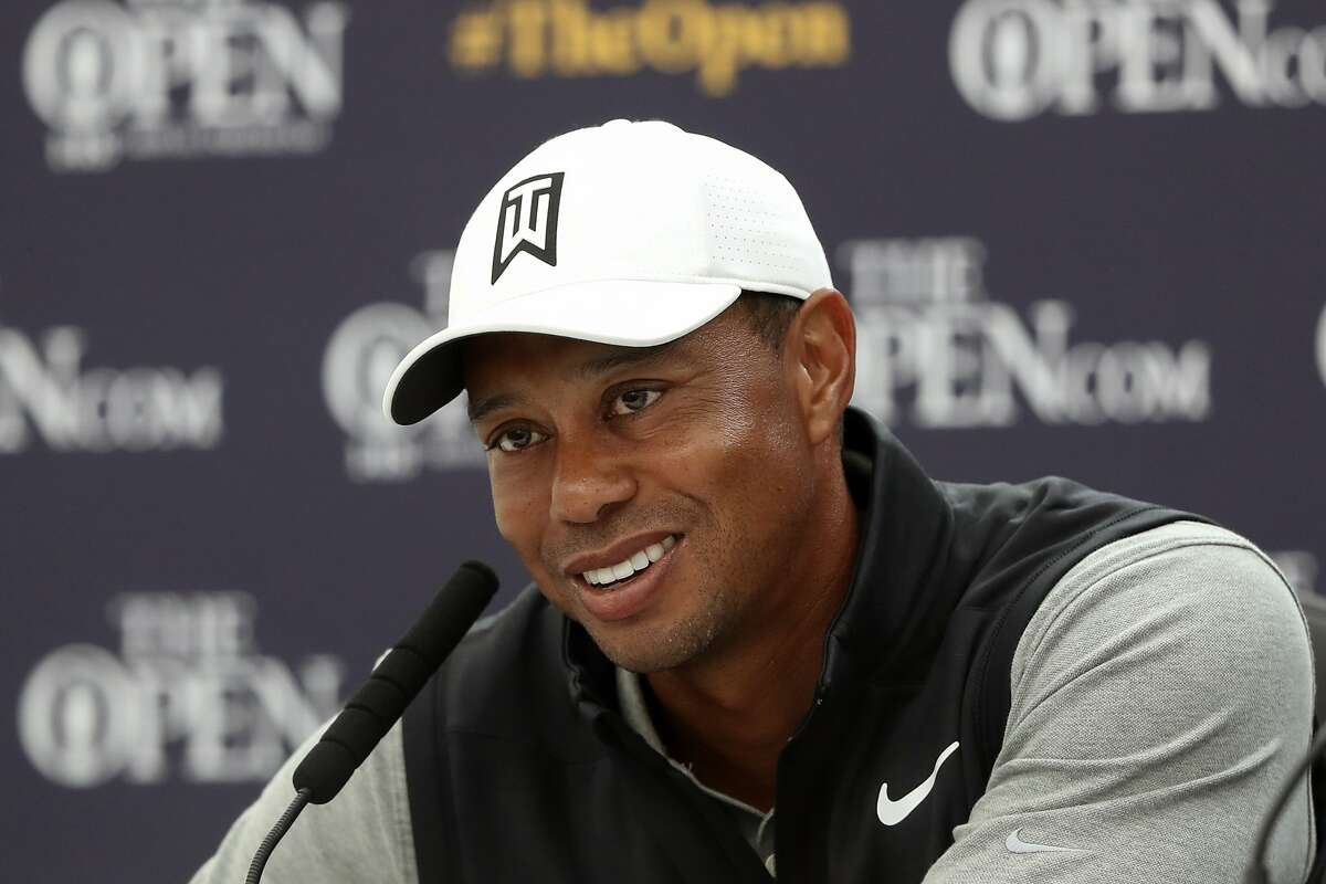 FILE - In this July 16, 2019, file photo, Tiger Woods speaks at a press conference ahead of the start of the British Open golf championships at Royal Portrush in Northern Ireland. Tiger Woods is writing what he describes as his definitive story in a memoir titled