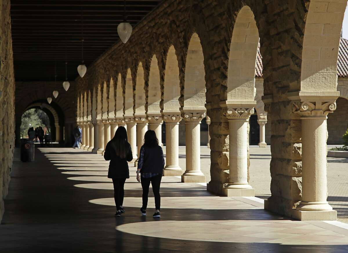 FILE - In this March 14, 2019, file photo students walk on the Stanford University campus in Santa Clara, Calif. When college students paying their own way have a financial hiccup, they have to make hard choices about how to spend their limited funds, and some turn to their food budget to close a gap. (AP Photo/Ben Margot, File)