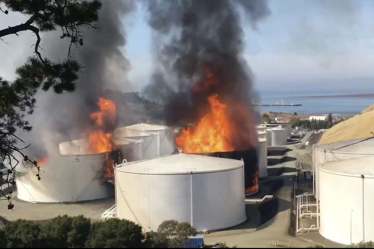 In this image from video provided by the Napa County Sheriff's Office, tanks are on fire at an oil storage facility Tuesday, Oct. 15, 2019, viewed from Rodeo, Calif. A fire burning at NuStar Energy LP facility in Crockett, Calif, in the San Francisco Bay Area prompted a hazardous materials emergency that led authorities to order the residents of two communities, Crockett and Rodeo, Calif., to shelter in place and stay inside with all windows and doors closed. Contra Costa Fire Department spokesman Steve Hill said that an hour into battling the blaze, firefighters seemed to be making progress and were continuing to keep adjacent tanks cooled with water. (Henry Wofford/Napa County Sheriff's Office via AP)
