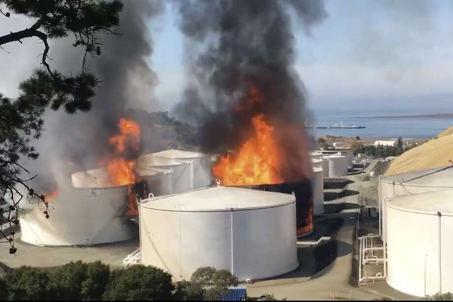 In this image from video provided by the Napa County Sheriff's Office, tanks are on fire at an oil storage facility Tuesday, Oct. 15, 2019, viewed from Rodeo, Calif. A fire burning at NuStar Energy LP facility in Crockett, Calif, in the San Francisco Bay Area prompted a hazardous materials emergency that led authorities to order the residents of two communities, Crockett and Rodeo, Calif., to shelter in place and stay inside with all windows and doors closed. Contra Costa Fire Department spokesman Steve Hill said that an hour into battling the blaze, firefighters seemed to be making progress and were continuing to keep adjacent tanks cooled with water. (Henry Wofford/Napa County Sheriff's Office via AP) Photo: Henry Wofford, Associated Press