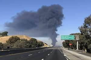 Interstate 80 is closed as a fire at an oil storage facility burns in the background Tuesday, Oct. 15, 2019, in Rodeo, Calif. A fire burning at NuStar Energy LP facility in Crockett, Calif., in the San Francisco Bay Area prompted a hazardous materials emergency that led authorities to order the residents of two communities, including Rodeo, to stay inside with all windows and doors closed. Contra Costa Fire Department spokesman Steve Hill said that an hour into battling the blaze, firefighters seemed to be making progress and were continuing to keep adjacent tanks cooled with water. (AP Photo/Ben Margot)