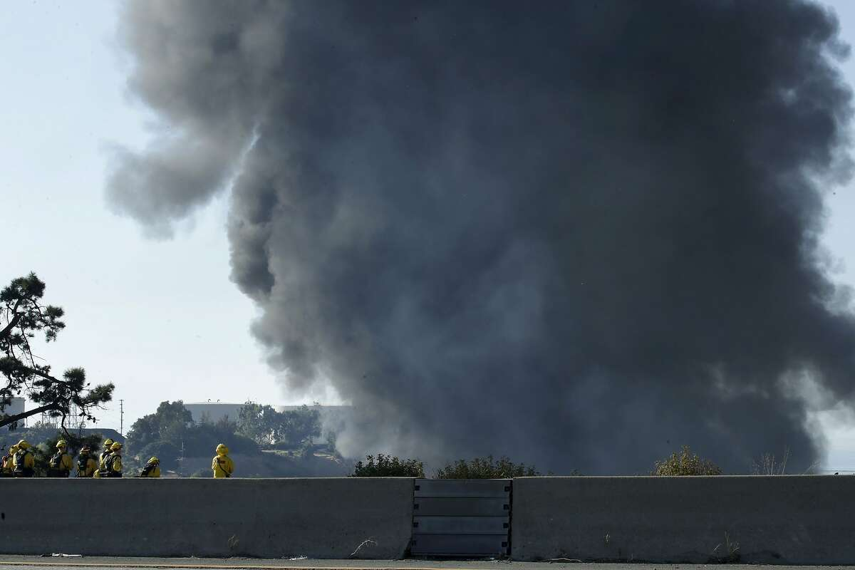 Firefighters, left, monitor a fire at an oil storage facility from westbound Interstate 80 Tuesday, Oct. 15, 2019, in Crockett, Calif. A fire burning at NuStar Energy LP facility in Crockett, prompted a hazardous materials emergency that led authorities to order the residents of two communities, including Rodeo, to stay inside with all windows and doors closed. Thick plumes of black smoke and flames filled the skyline around the facility, about 30 miles northeast of San Francisco. (AP Photo/Ben Margot)