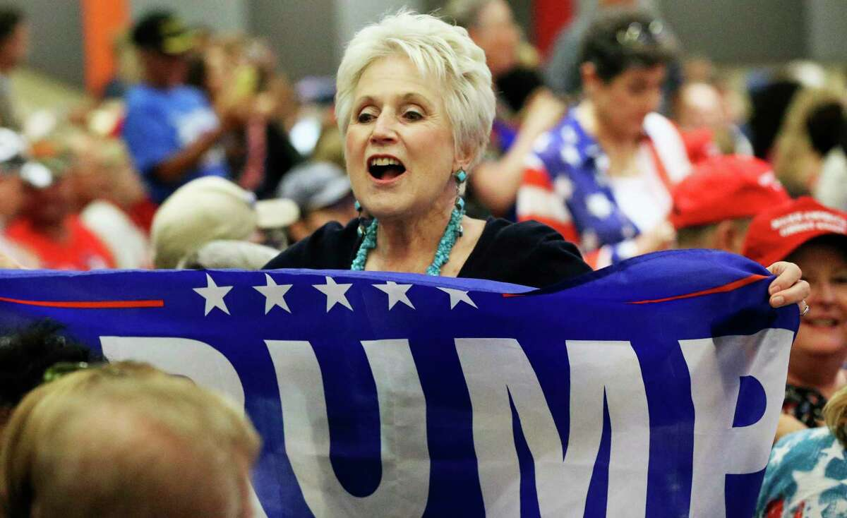 Kay Turner unfurls a banner as Donald Trump, Jr. visits the Henry B. Gonzalez Convention Center on behalf of the Trump/Pence 2020 rel-election campaign on Oct. 15, 2019.