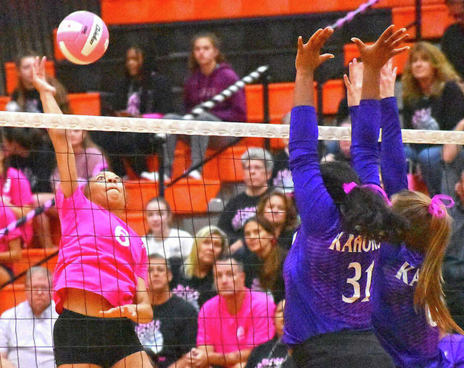 Edwardsville's Alexa Harris, left, prepares to slam down one of her match-high nine kills. Photo: Matt Kamp|The Intelligencer