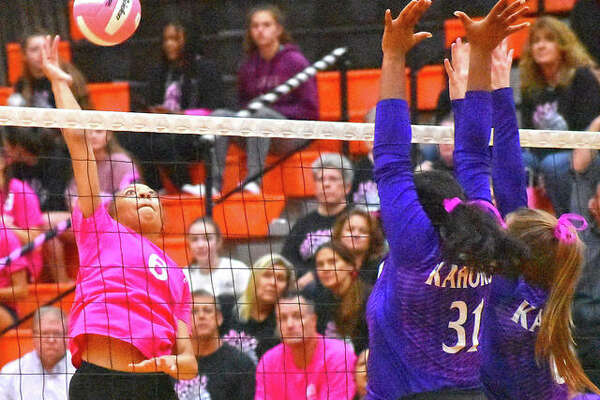 Edwardsville's Alexa Harris, left, prepares to slam down one of her match-high nine kills.