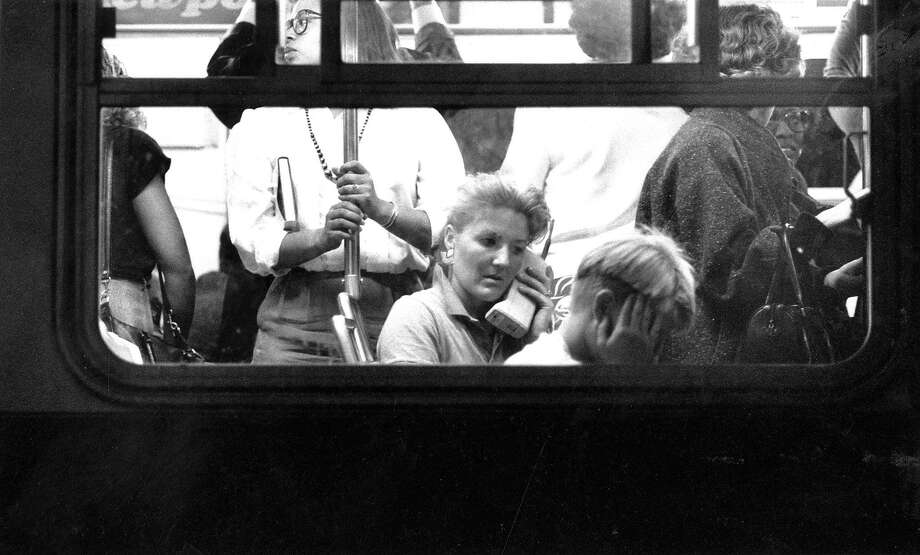 Woman in a crwded bus in San Francisco uses a cellular phone to commmunicate after the Loma Prieta earthquake October 17, 1889  Photo ran 10/18/1989 P.A6, Photo: Steve German / The Chronicle 1989