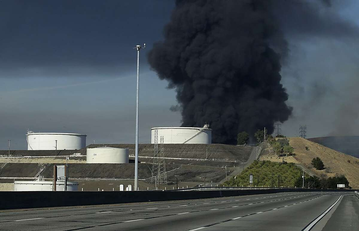 """Interstate 80 is closed as a fire at an oil storage facility burns Tuesday, Oct. 15, 2019, in Crockett, Calif. A fire burning at NuStar Energy LP facility prompted a hazardous materials emergency that led authorities to order the residents of two communities, including Rodeo, to stay inside with all windows and doors closed. """"This is a very dynamic, rapidly evolving situation,"""" Capt. George Laing of the Contra Costa Fire Department said. (AP Photo/Ben Margot)"""