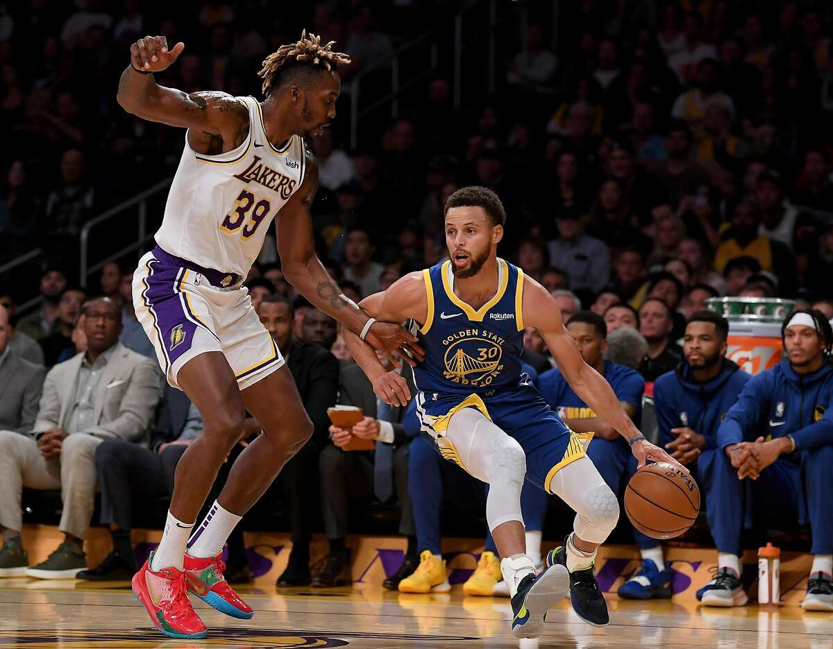 FILE PHOTO: Stephen Curry, right, of the Golden State Warriors dribbles in front of Dwight Howard, left, of the Los Angeles Lakers during the first half at Staples Center on October 14, 2019 in Los Angeles.