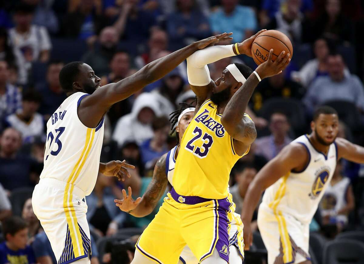 LeBron James #23 of the Los Angeles Lakers is guarded by Draymond Green #23 of the Golden State Warriors at Chase Center on October 05, 2019 in San Francisco, California.