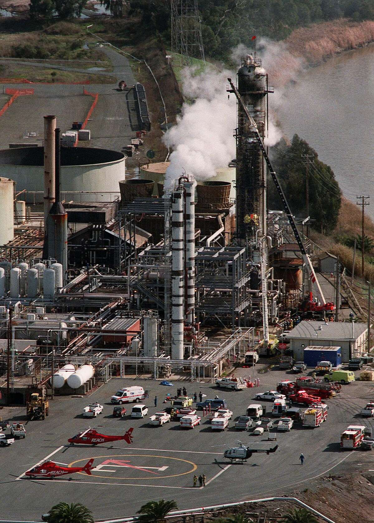 Emergency helicopters and ambulances stand by at Tosco refinery in Martinez, Calif., where an explosion and fire took place Tuesday, Feb. 23, 1999. Firefighters in yellow, halfway up the scaffolding on the largest tower at right, climb up the scaffolding to get to the victims. As of 4:30 pm Tuesday, officials said one oil worker was killed and at least four others were seriously injured following the explosion. (AP Photo/Contra Costa Times, Susan Pollard) ALSO RAN: 03/16/1999, 4/24/2000,
