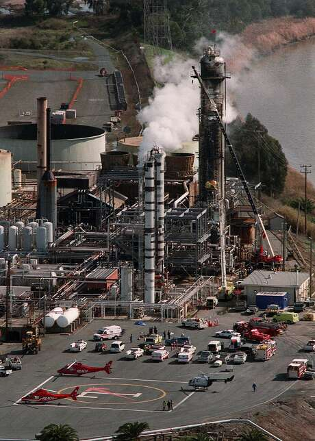 Emergency helicopters and ambulances stand by at Tosco refinery in Martinez, Calif., where an explosion and fire took place Tuesday, Feb. 23, 1999. Firefighters in yellow, halfway up the scaffolding on the largest tower at right, climb up the scaffolding to get to the victims. As of 4:30 pm Tuesday, officials said one oil worker was killed and at least four others were seriously injured following the explosion. (AP Photo/Contra Costa Times, Susan Pollard) ALSO RAN: 03/16/1999, 4/24/2000, Photo: SUSAN POLLARD