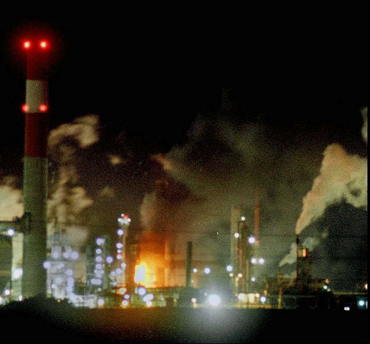 Flames can be seen at the Tosco Refinery Co. following an explosion Tuesday night Jan. 21, 1997 near Martinez, Calif. The fire was located in the center of the refinery seen here from about a mile away. (AP Photo/Contra Costa Times, Damien Stark)