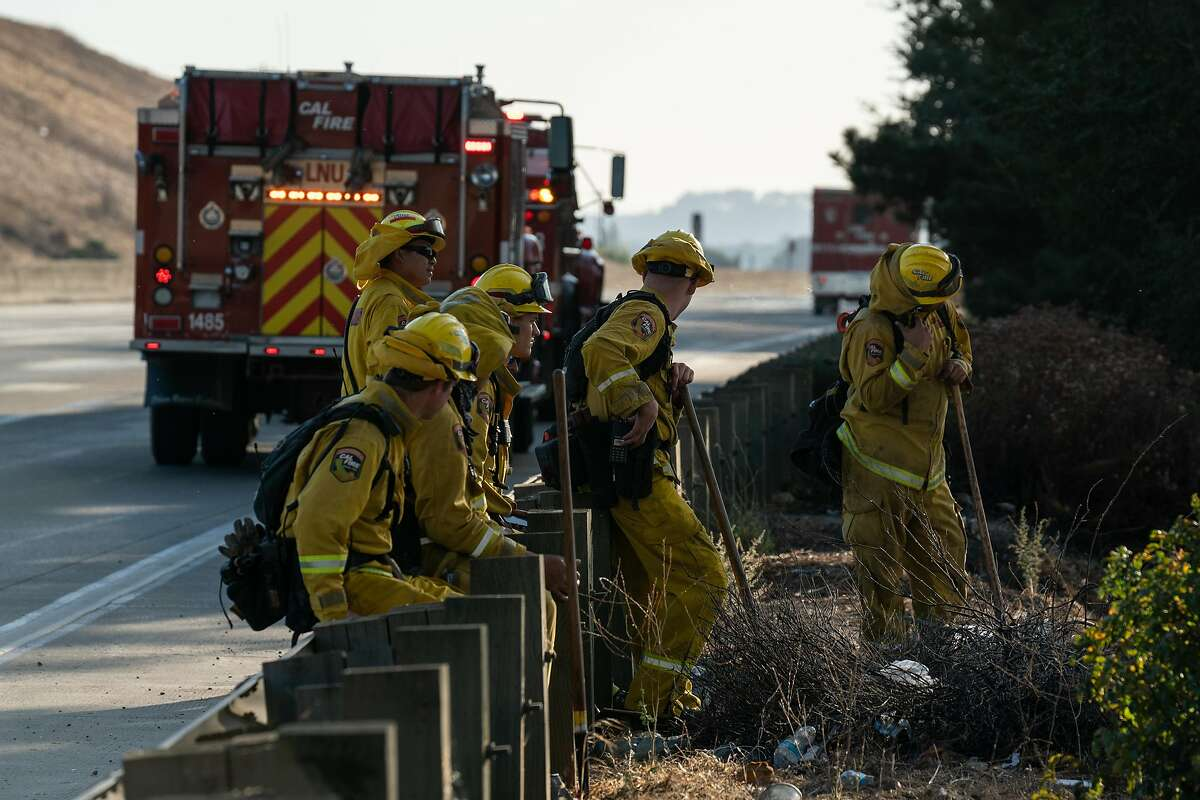 A Cal Fire crew takes a break after working to extinguish flames at NuStar energy facility in Crockett, Calif. on Tuesday, Oct. 15, 2019.