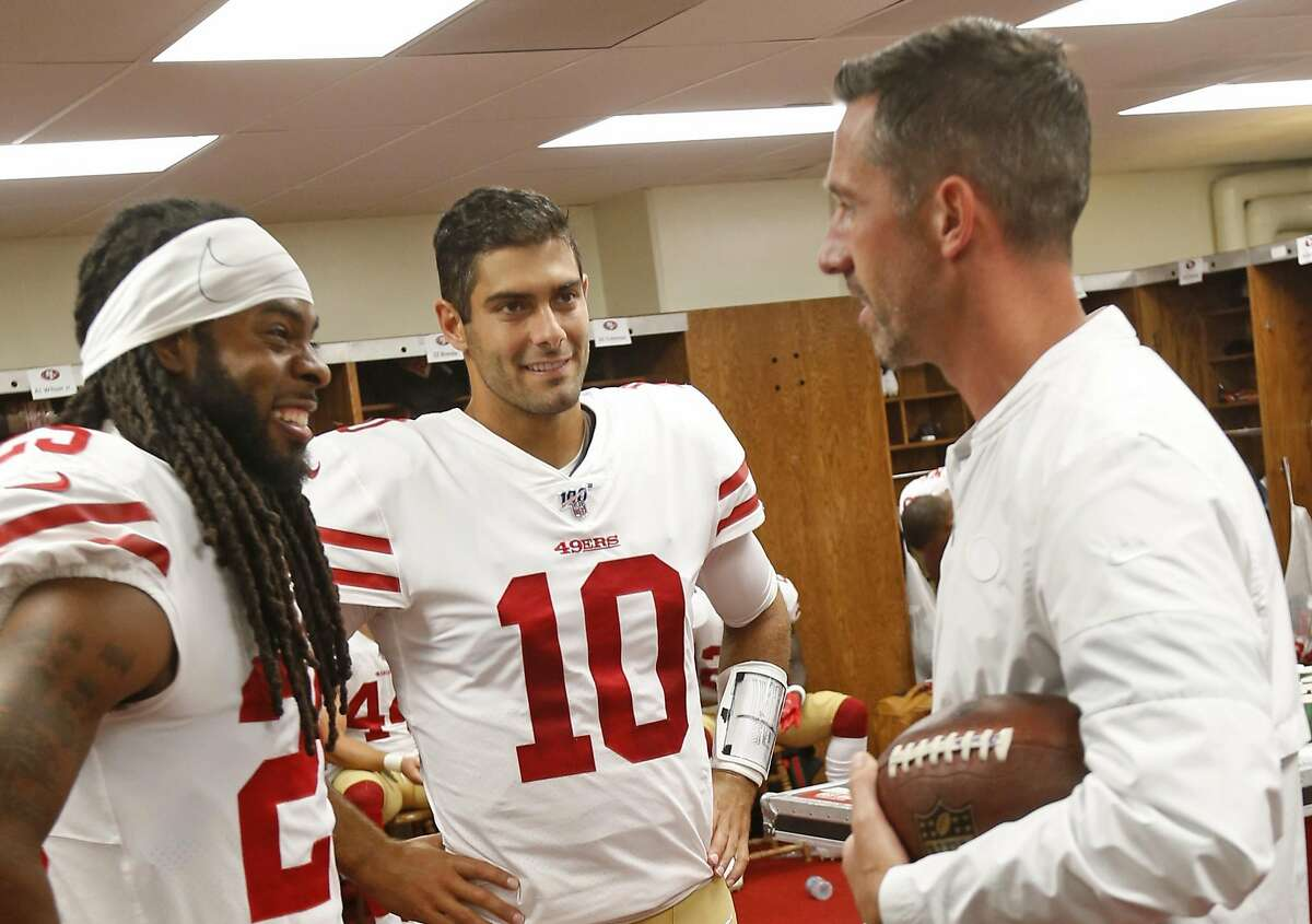 Richard Sherman #25, Jimmy Garoppolo #10 and Head Coach Kyle Shanahan of the San Francisco 49ers talk in the locker room prior to game against the Kansas City Chiefs at Arrowhead Stadium on August 24, 2019 in Kansas City, Miss